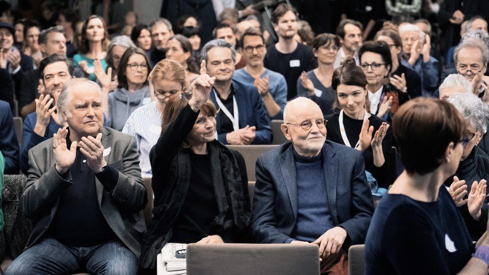 Supertotale von den Stuhlreihen während der Mitgliederversammlung. Senta Berger neben Michael Verhoeven und Günther Rohrbach in einer der ersten Reihen. Die Mitglieder klatschen, Senta Berger hebt den Finger in die Luft.