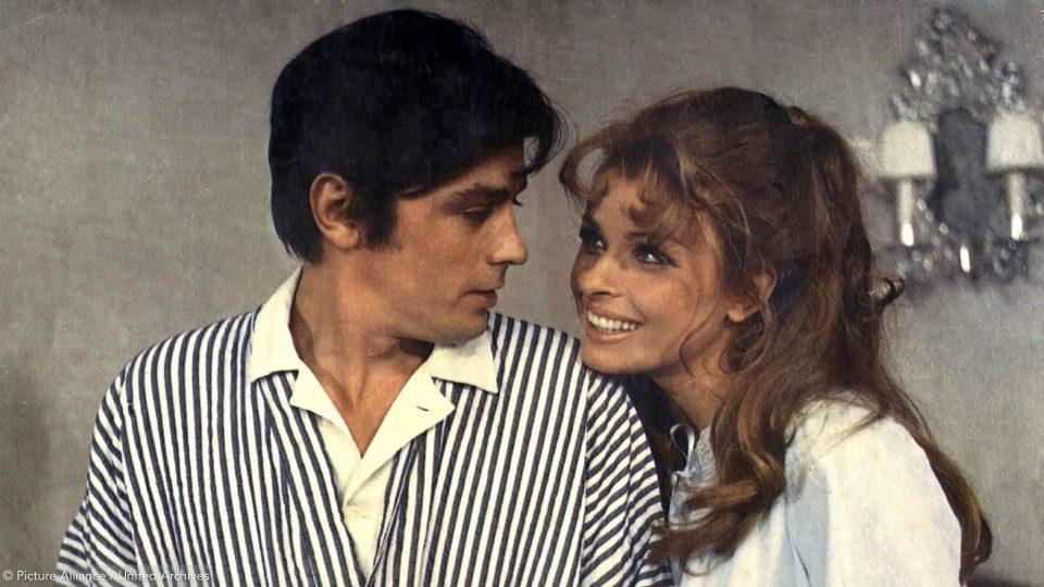 Ein altes Bild von Senta Berger als junge Frau mit langem Haar. Sie steht neben dem Schauspieler Alain Delon. Die beiden schauen sich vertraut an.