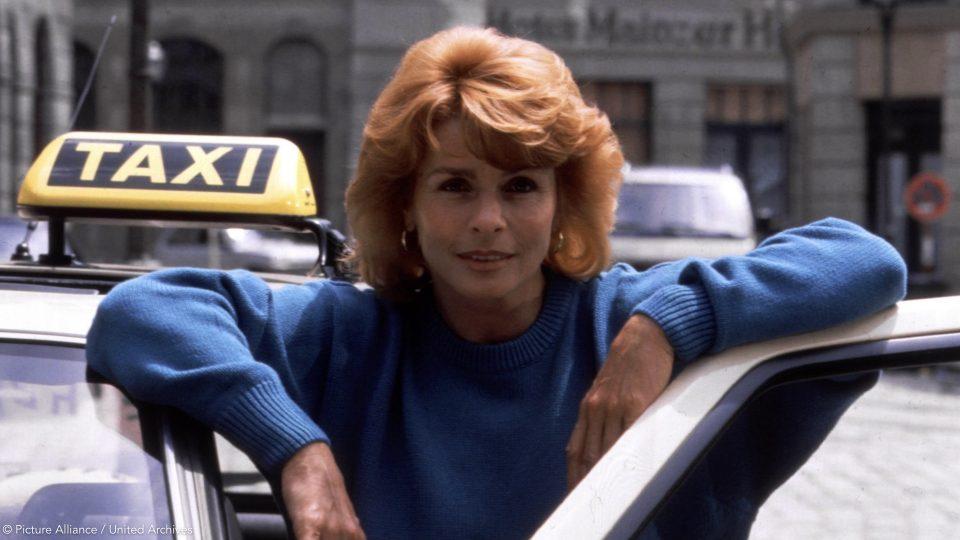 Ein altes Bild von Senta Berger aus den 1980er Jahren mit einer typischen 1980er Frisur, sehr voluminöses Haar bis zu den Schulter und einem Pony. Sie steht an der offenen Tür eines Taxis auf der Fahrerseite.
