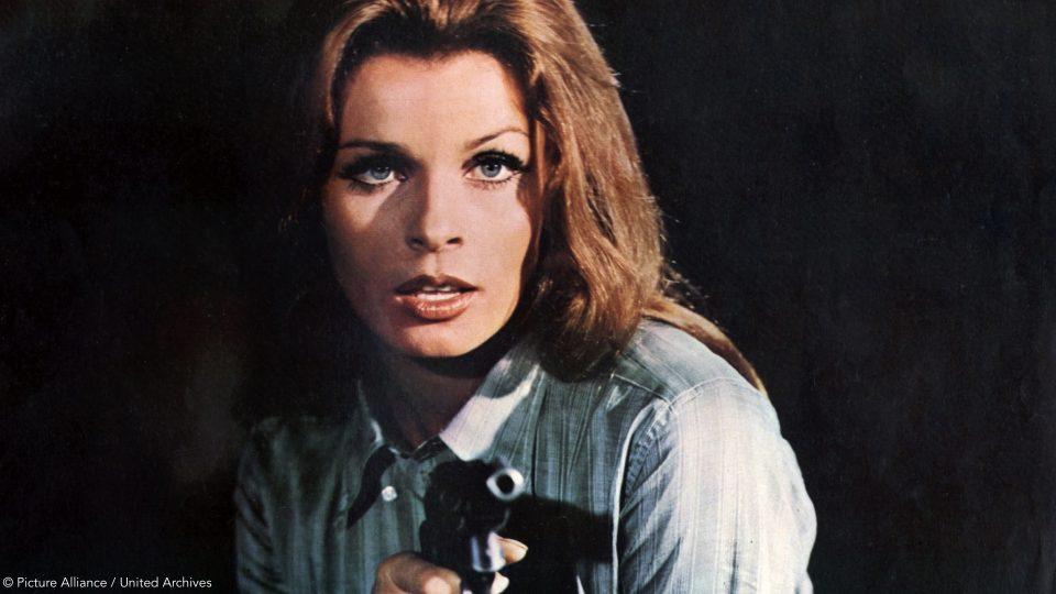 Ein altes Bild von Senta Berger als junge Frau. Sie trägt ihr Haar lang und hält eine Pistole, die auf die Kamera hingerichtet zielt.