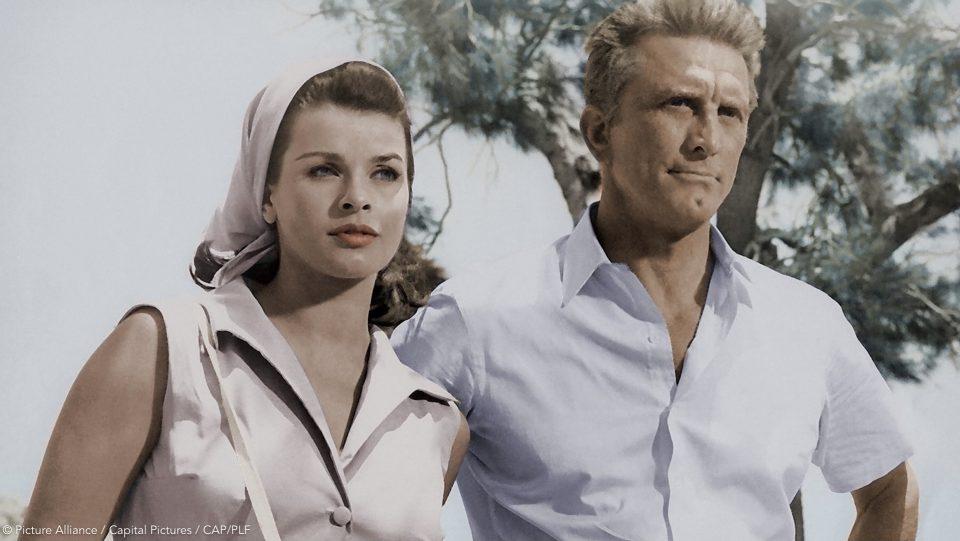 Ein altes Bild von Senta Berger als junge Frau. Sie steht neben dem Schauspieler Kirk Douglas draußen vor einem Baum. Senta trägt ein Blusenkleid und ihre Haare sind von einem Tuch bedeckt.