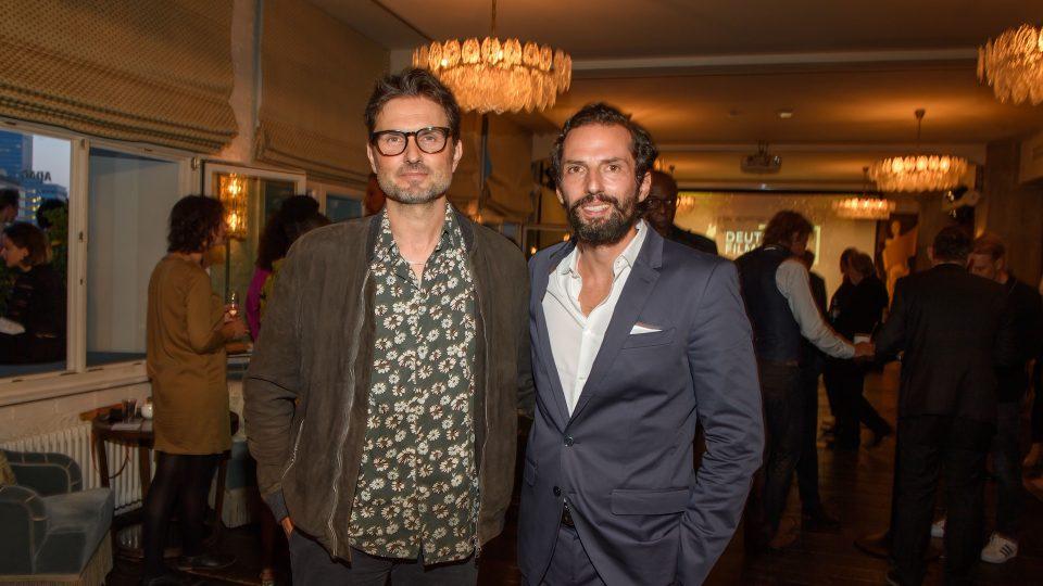 Rechts Quirin Berg im dunkelgrauen Anzug mit offenem weißen Hemd, und rechts Simon Verhoeven im Blumen gemusterten Hemd und brauner Jacke. Beide lächeln in die Kamera.