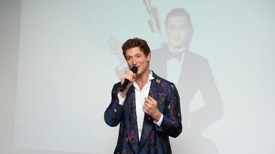 Daniel Donskoy spricht in einer Handmikrofon. Im Hintergrund auf einer Leinwand wir das aktuelle Pressefoto von Donskoy als diesjähriger Moderator des Filmpreises projiziert. Er trägt einen gemusterten langen dunkelblauen Mantel, darunter ein weißes Hemd.