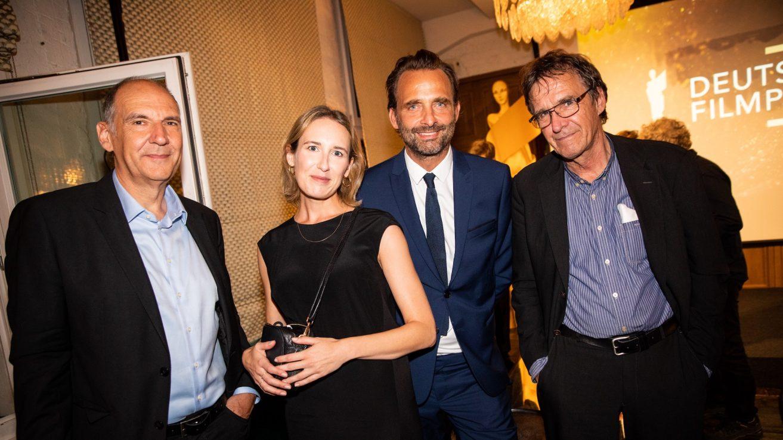 Gruppenbild. Ganz links Michael Düwel, danben Bianca Makarewicz und Eike Wolf. Alle schauen in die Kamera. Im Hintegrund sieht man Leinwand im Saal, auf der das Filmpreis-Logo projiziert ist.