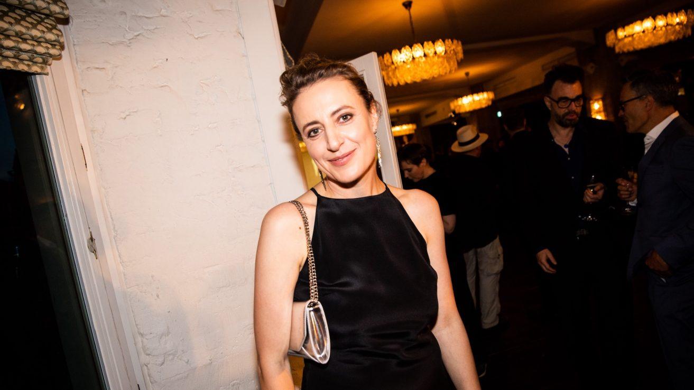 Halbnahe Aufnahme von Maren Eggert. Sie trägt ein schwarzes Abendkleid, das bis zum Hals geht. Ihre Schulter sind nicht bedeckt. Die trägt lange hängende goldene Ohrringe und eine silbene kleine Handtasche ist über ihre Schulter gehangen. Sie lächelt in die Kamera.