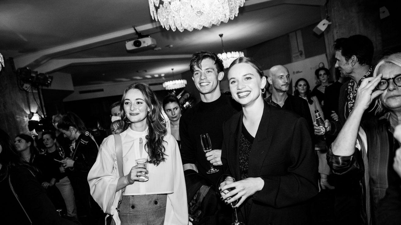 Totale vom Publikum, das auf die Bühne schaut. Im Vordergrund befinden sich Maria Ehrich, neben Jannis Niewöhner und Luna Wedler. Sie halten alle einen Drink in der Hand und lächeln stark.