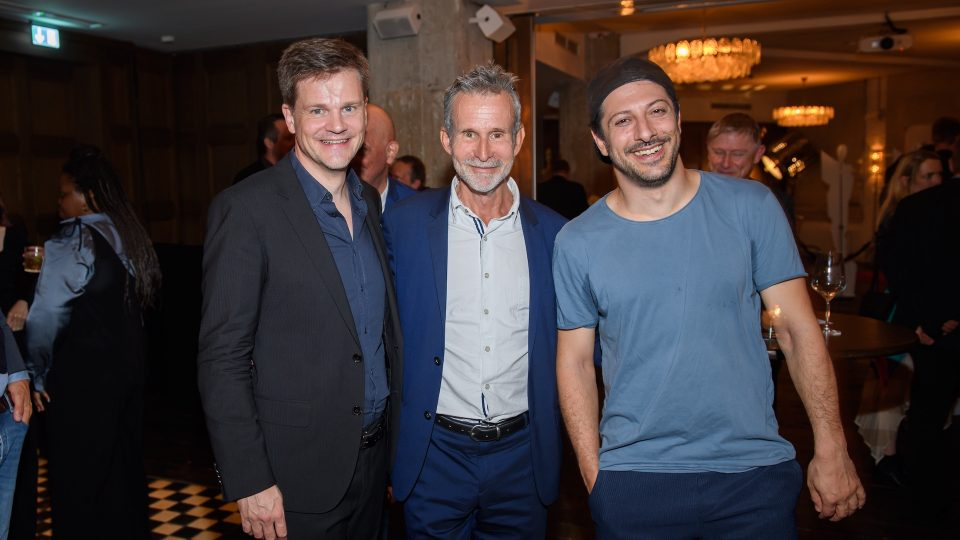 Gruppenbild von Benjamin Herrmann, Ulrich Matthes und Fahri Yardim. Alle drei lächeln in die Kamera. Herrman und Matthes in Anzug, Yardim leger in Tshirt. Im Hintergrund sieht man Gäste, die feiern.
