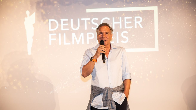 Nico Hofmann vor der Leinwand, auf der das Filmpreis-Logo projiziert ist. Er hält ein schwarzes Handmikrofon in der Hand und spricht rein. Er trägt ein hellblaues Hemd und hat einen Pulli um die Hüften geknotet.