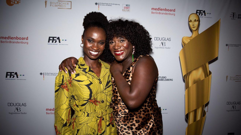 Lorna Ishema und Thelma Buanbeng stehen eng an einander vor der Pressewand, neben ihnen die goldene Papp-Lola-Statue. Ishema trägt ein gelb-grünes gemustertes Kleid, Buabeng ein Kleid mit Leoprint. Buabeng hält ihren Arm um Ishemas Schulter. Beide lächeln stark in die Kamera.
