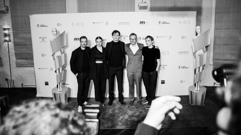 Das Team von dem Film JE SUIS Karl, Christian Schwochow, Luna Wedler, Jannis Niewöhner, Christoph Friedel und Claudia Steffen stehen vor der Pressewand. Neben ihnen jeweils eine Papp-Lola-Statue. Im unteren vorderen Bereich des Bildes sieht man die Köpfe und Hände von den Fotografen aus der Presslane.