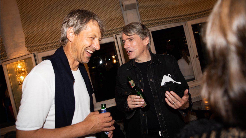 Daniel Saltzwedel links und Frank Kruse rechts. Beide halten eine Flasche Bier in ihrer Hand. Sie unterhalten sich und es herrscht eine ausgelassene Stimmung.