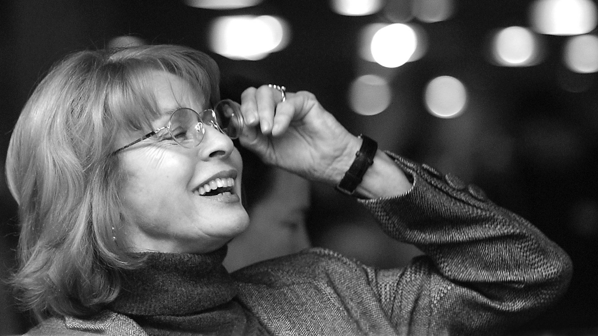 Schwarz weiß Bild von Senta Berger, sie lacht, ihre Augen sind vom Lachen geschlossen. Ihre Hand ist an ihrer Brille.